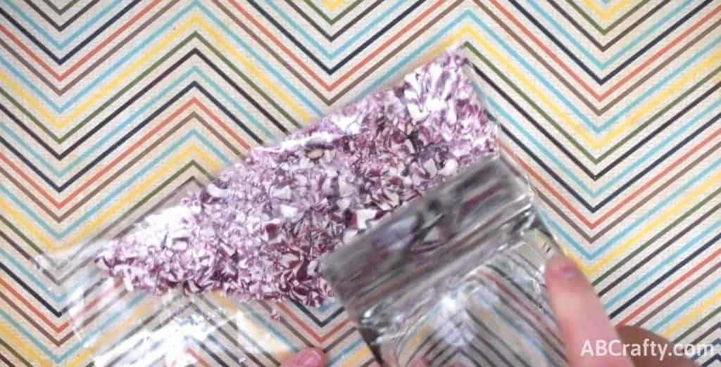 Crushing purple candies in a bag with a glass