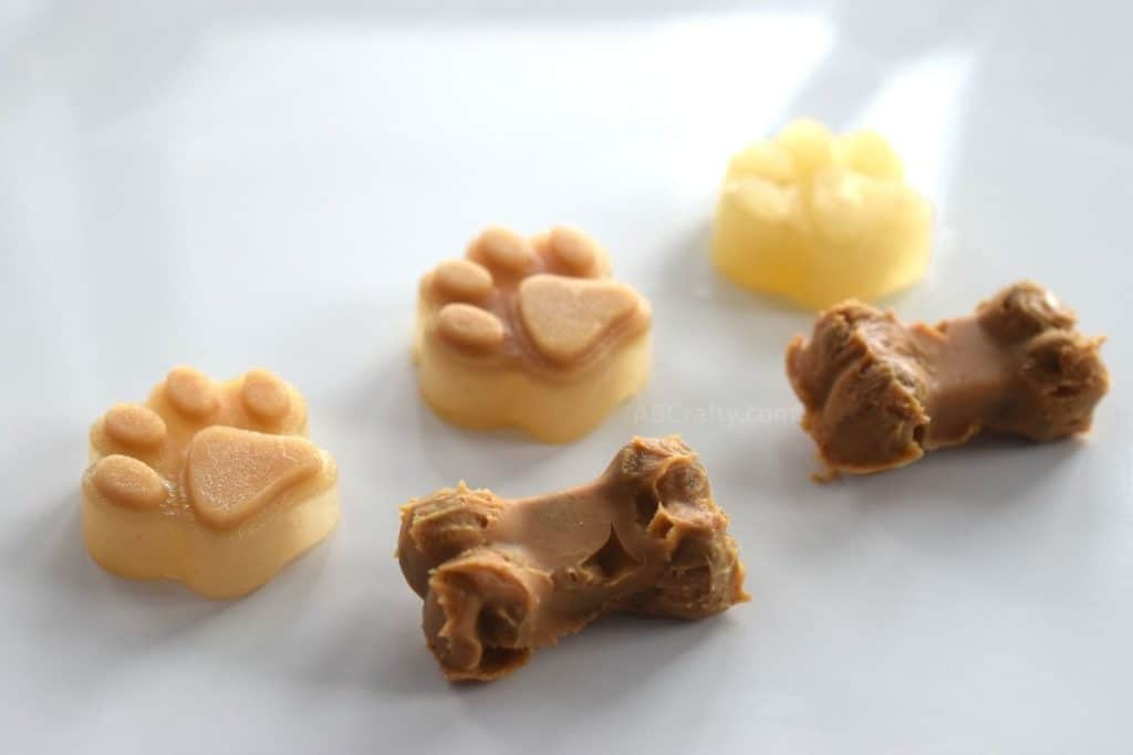 Homemade frozen dog treats in the shapes of paws and bones, made with peanut butter, apple sauce, and chicken broth. Commonly referred to as dog popsicles