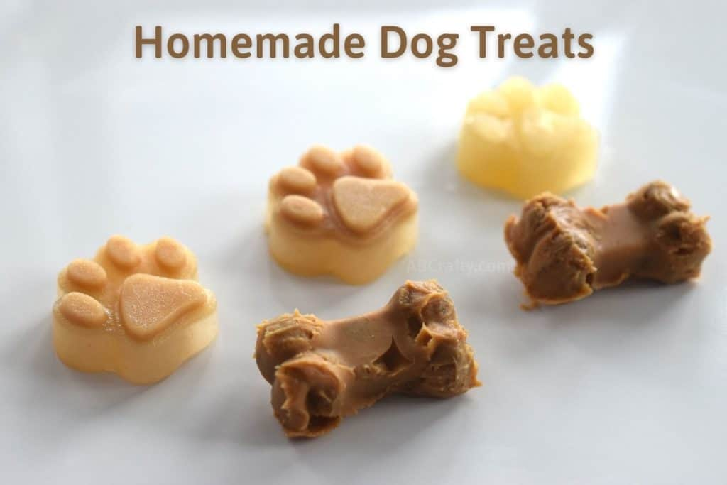 Homemade Dog Treats written over frozen dog popsicles made of peanut butter, sweet potato, and pumpkin. They're in the shape of puppy paws and little bones