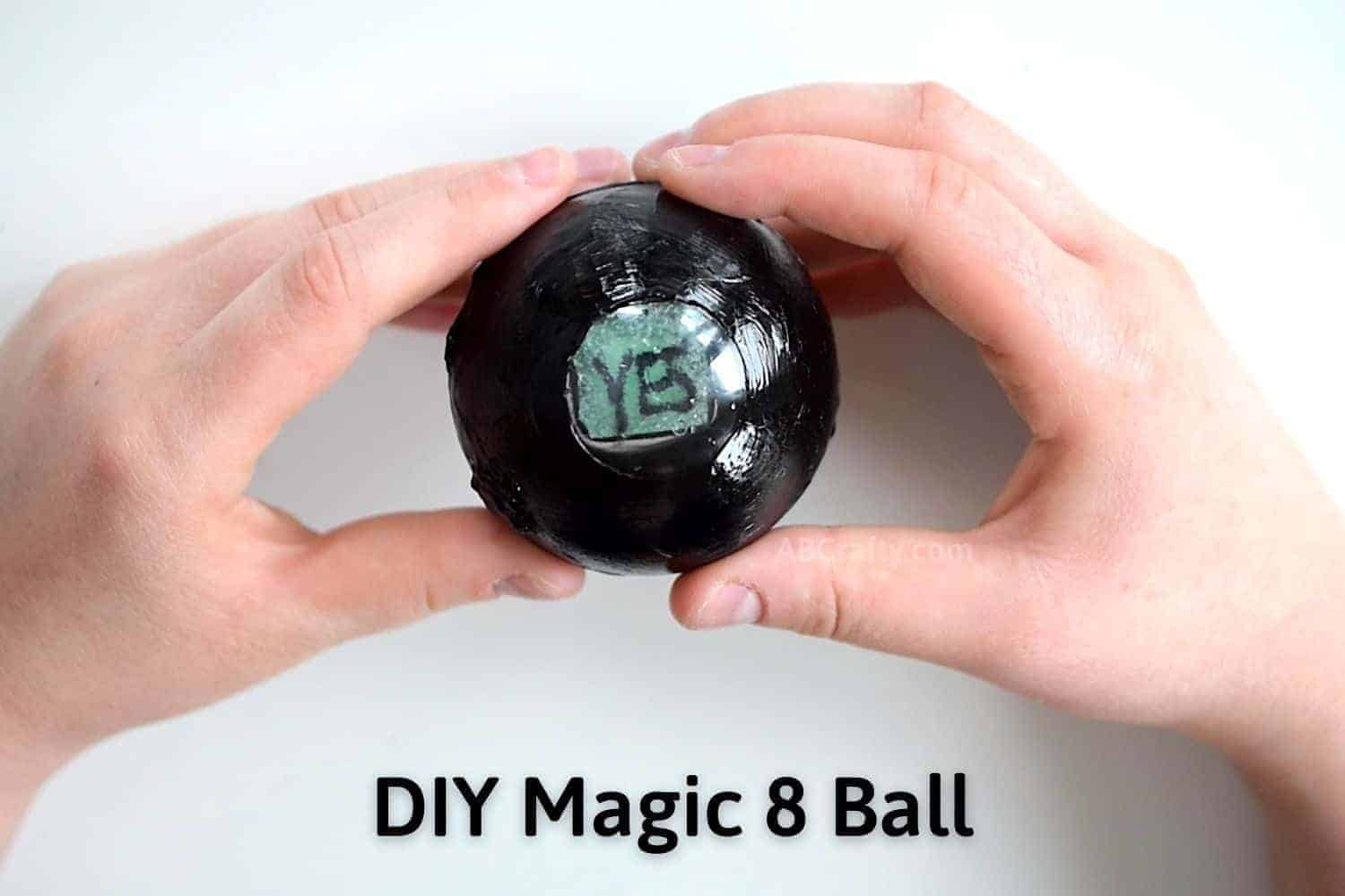 DIY Magic 8 Ball held in hands showing an answer of 'yes' with the words DIY Magic 8 Ball written on the image