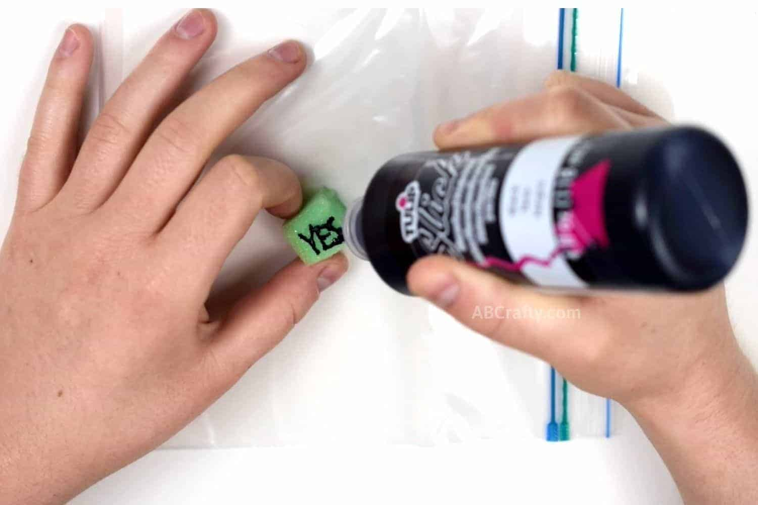 """Writing """"Yes"""" on a green foam cube with fabric paint that will be the answers for the magic 8 ball"""