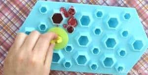 Placing the plastic from a ring pop onto the melted candy in the silicone mold