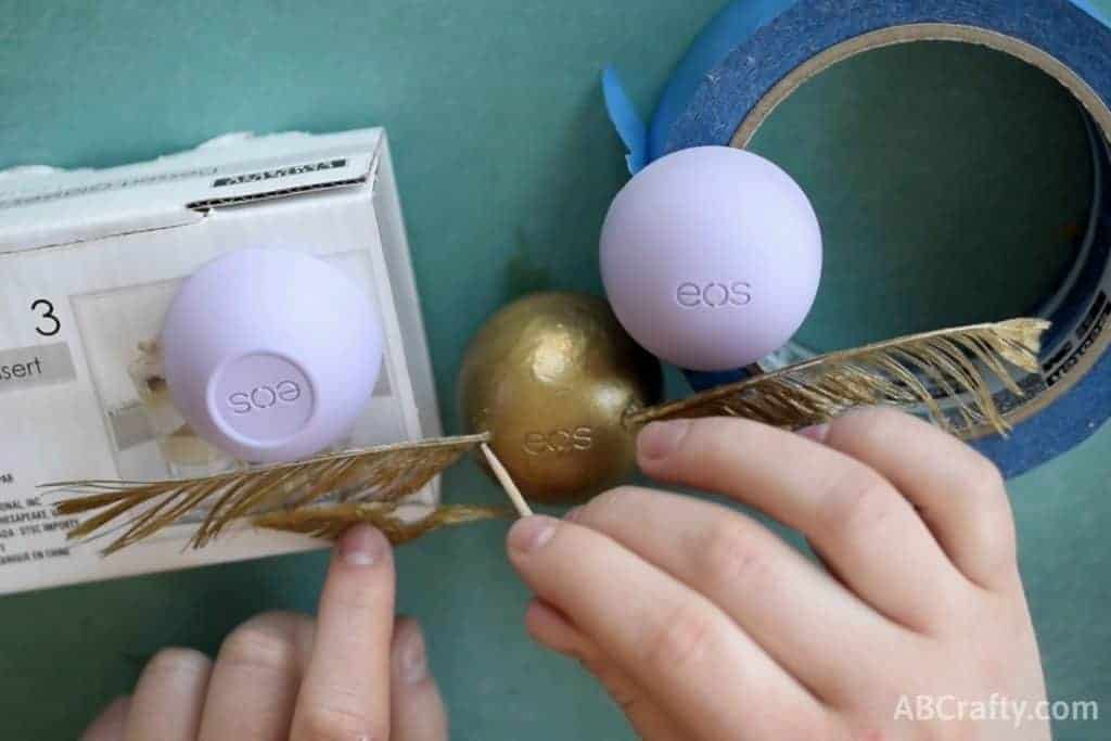 using a toothpick to attach the wings of the golden snitch