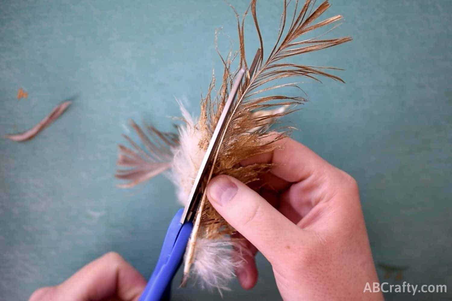 cutting the outside of off half of a feather that has been painted gold