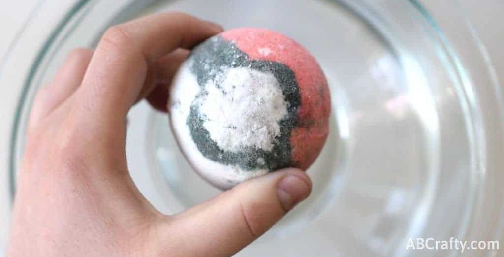 holding a bath bomb over water