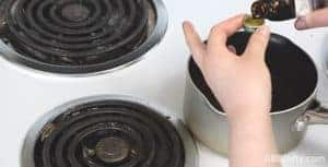measuring flavoring extract over a pot of cooked candy on the stove
