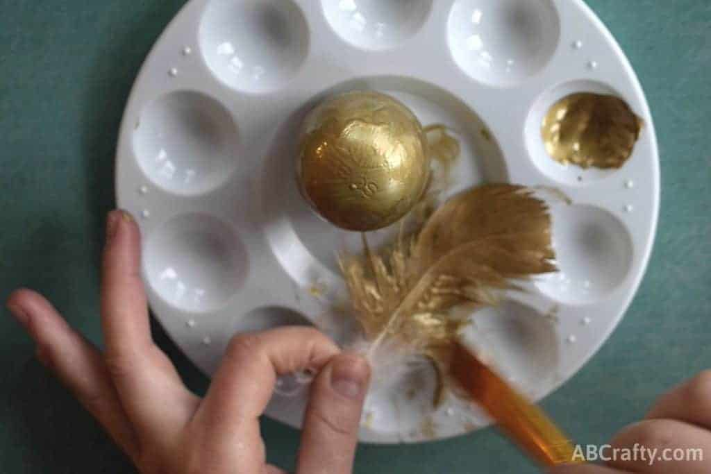 painting feathers with gold paint