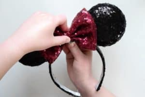 Adding red sequin bow to handmade light up minnie mouse ears