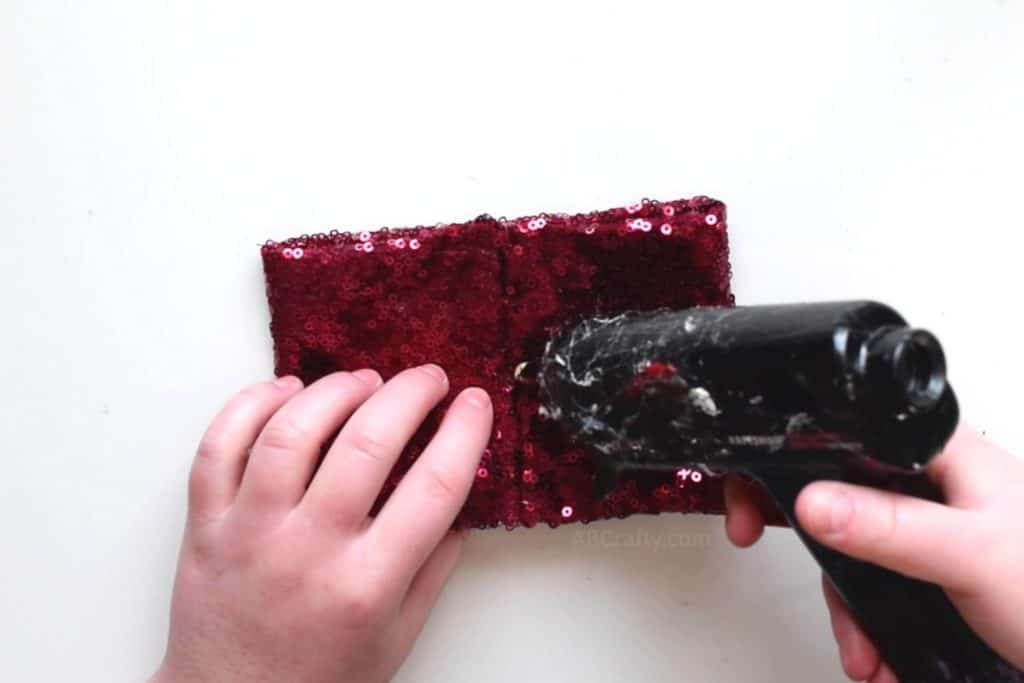 Using a glue gun to add glue to the middle of a rectangle of red sequin fabric