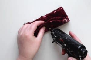 Adding glue to red sequin fabric