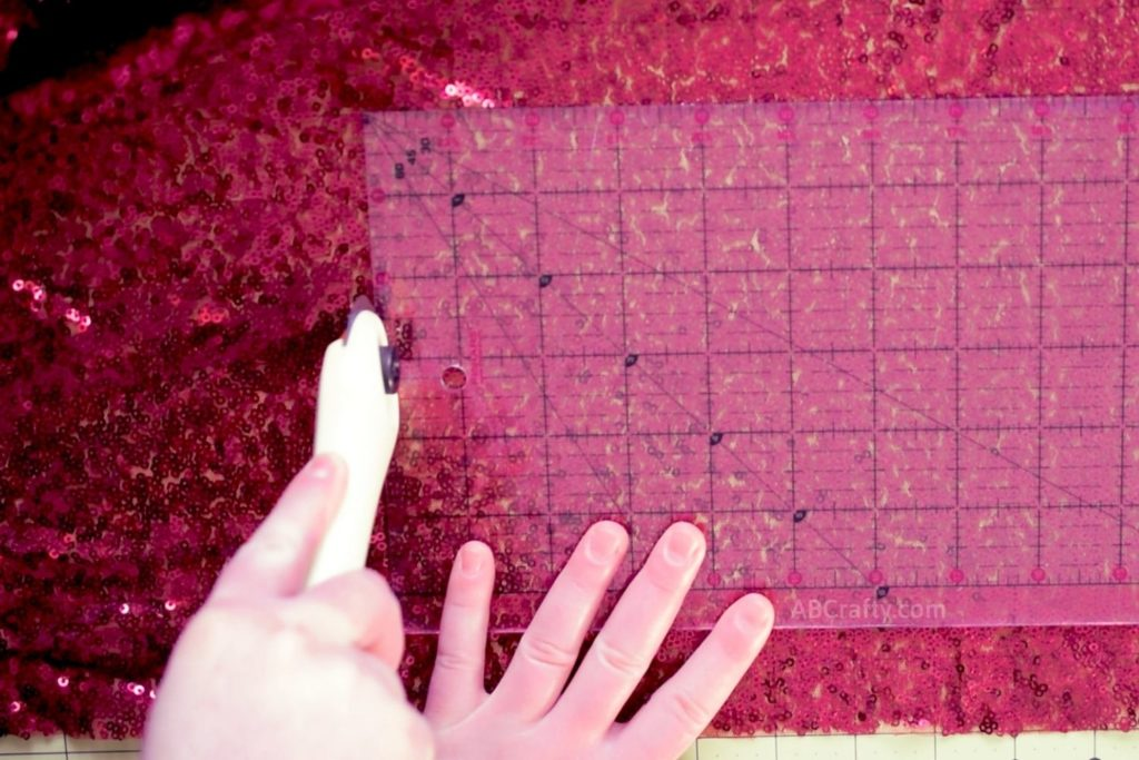 Using a rotary cutter to cut red sequin fabric using a ruler