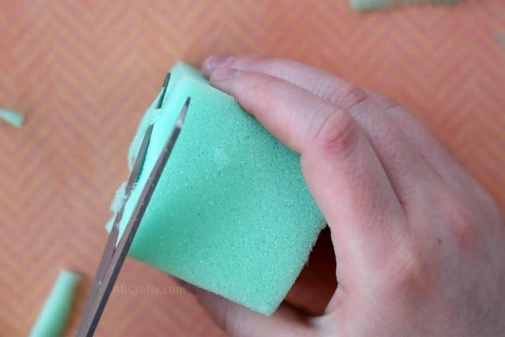 Cutting green foam into the shape of a cube with scissors