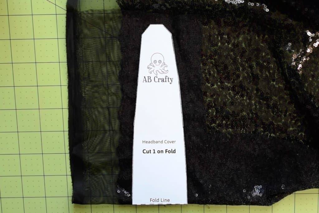 """Place the minnine mouse headband template on folded black sequin fabric so that the template lines up with the fold where it says """"fold line"""""""