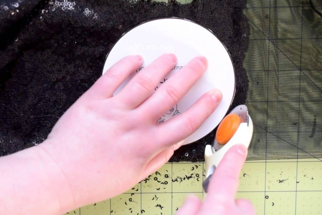Using a rotary cutter to cut along a printable minnie mouse ears template on black sequin fabric