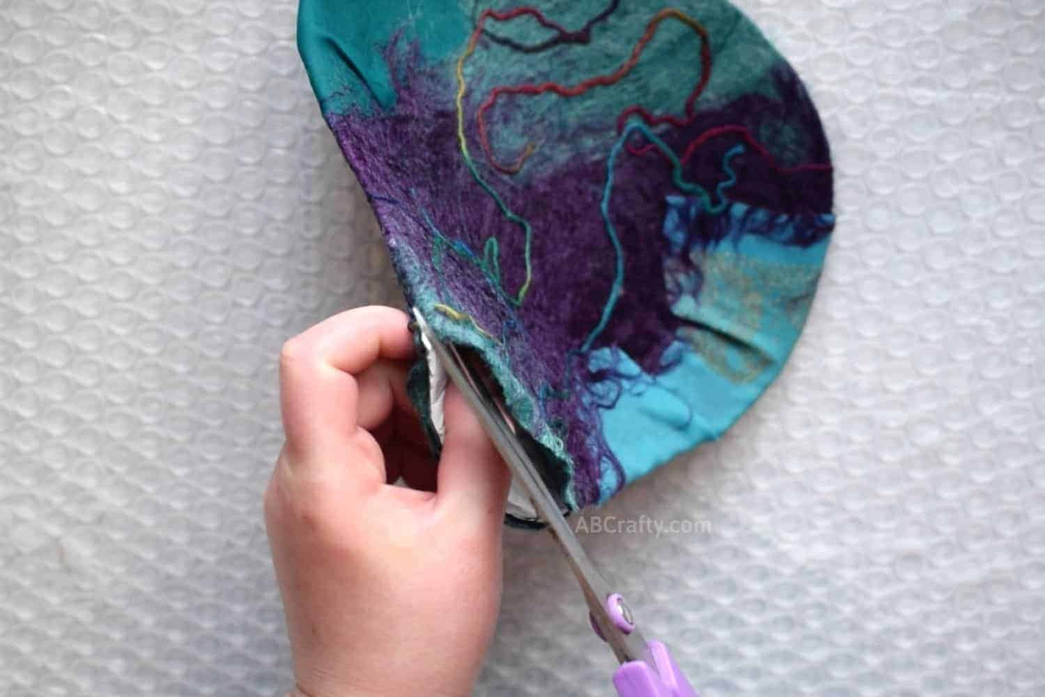 Using scissors to cut along the top of the lightly felted coin purse to remove the resist