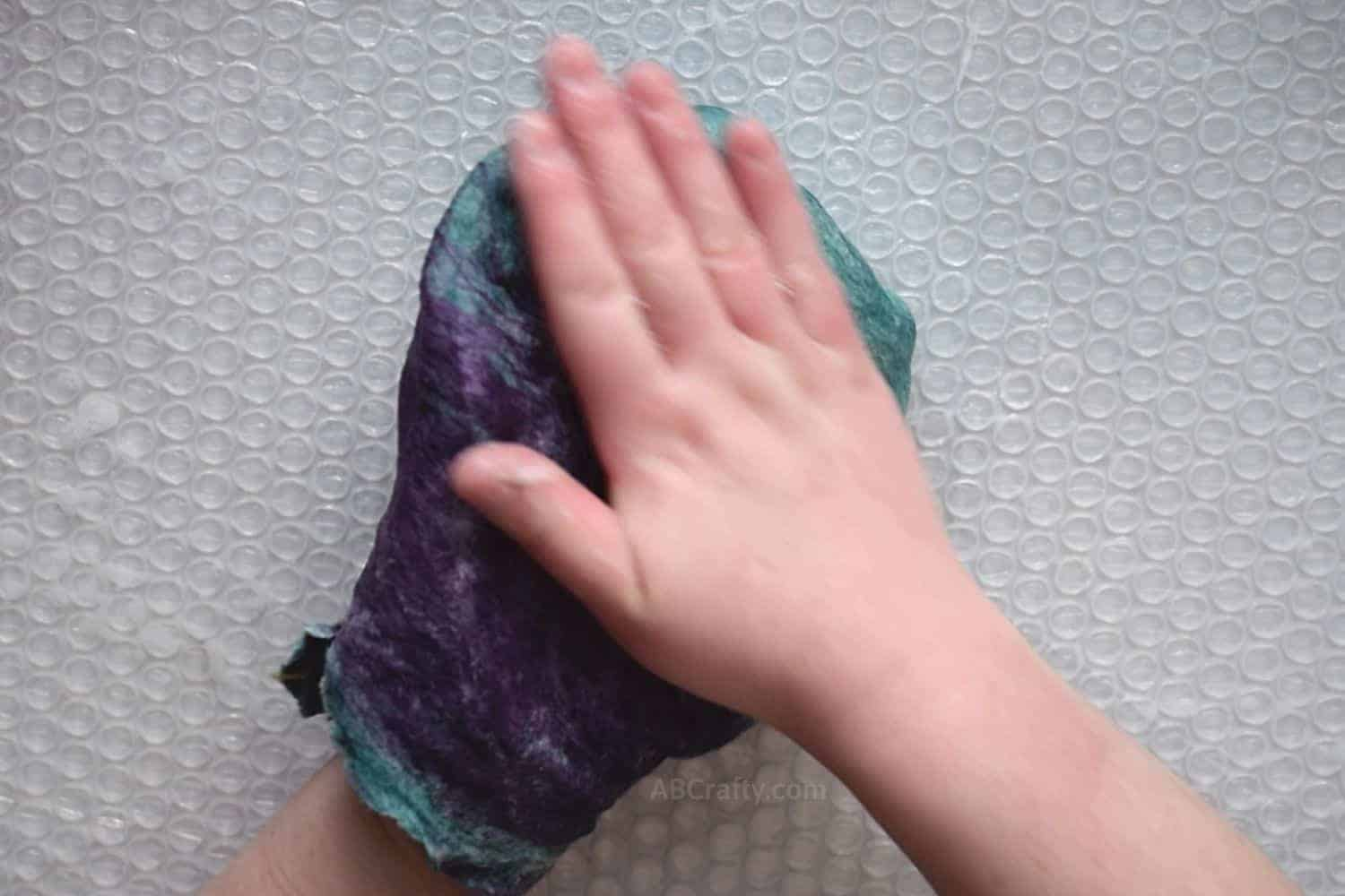 Rubbing the outside of a lightly felted pouch after flipping it inside out