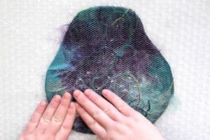 Using soapy hands to lightly rub fiber with a protective mesh in between