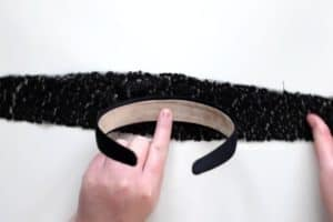 Glueing center of a black satin headband to a piece of black sequin fabric