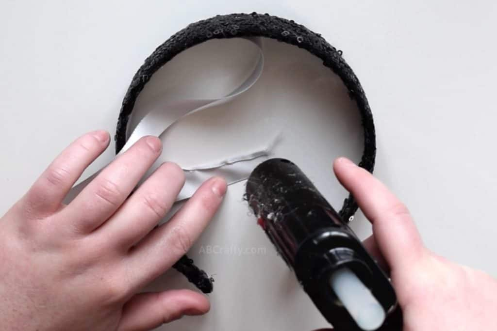 Using a glue gun to glue the sides of a white satin ribbon down. The ribbon is also attached to a black sequin headband.