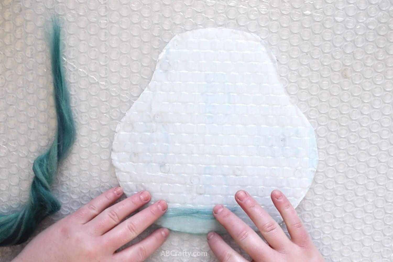 Laying first teal merino wool fibers on resist