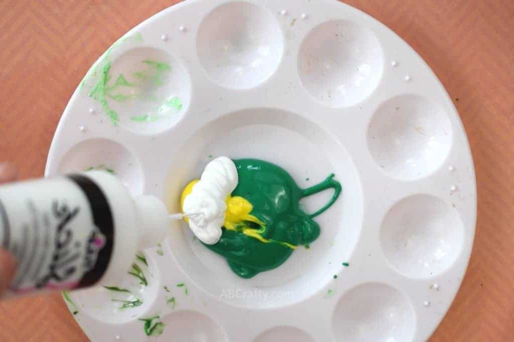 Squeezing white fabric paint into a mixing palette with green and yellow fabric paint