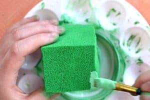 Using a paintbrush to paint light green fabric paint onto the edge of a green-painted foam block