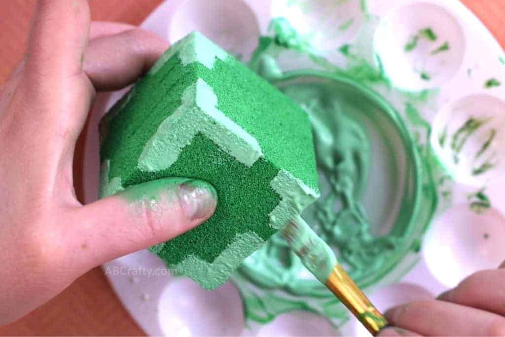Using paintbrush to paint all corners of painted green cube with stripes of light green fabric paint