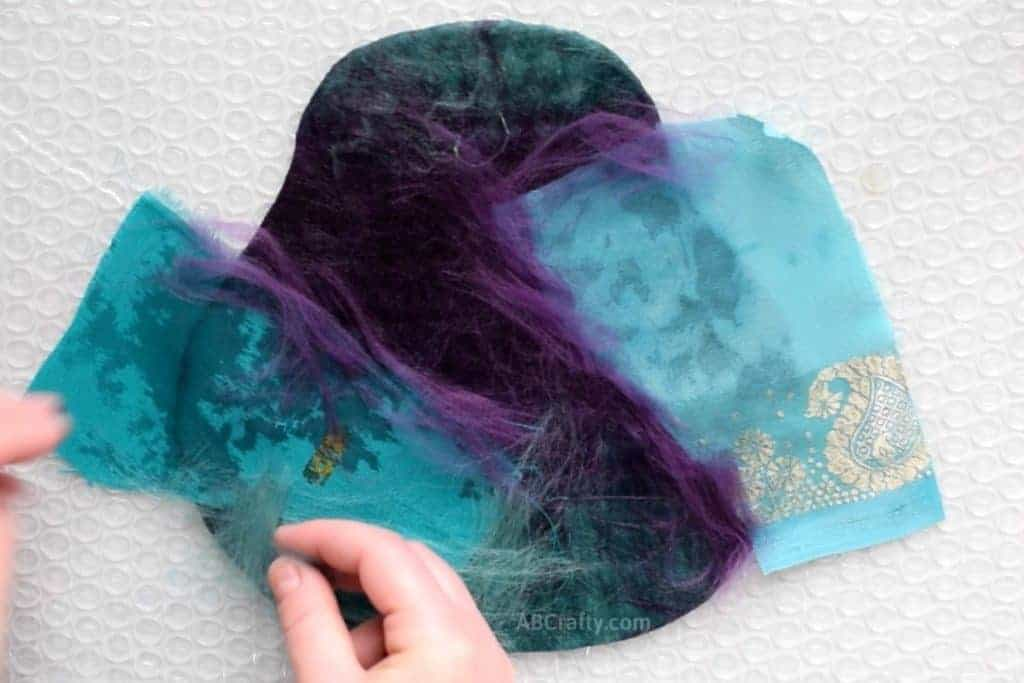 Placing teal and purple merino wool along the edges of scraps of blue and teal sari silk fabric to help it felt to the fiber below