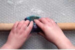 Rolling the wet felted project on a wooden dowel