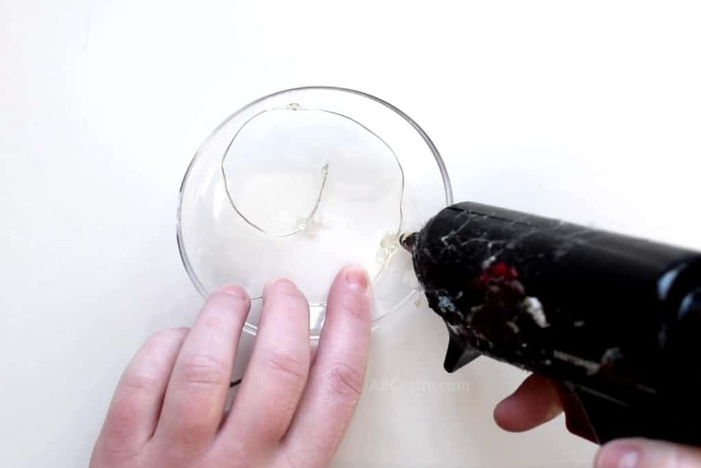 Using a glue gun to start glueing LED fairy lights in a spiral inside of half of a clear fillable plastic ornament