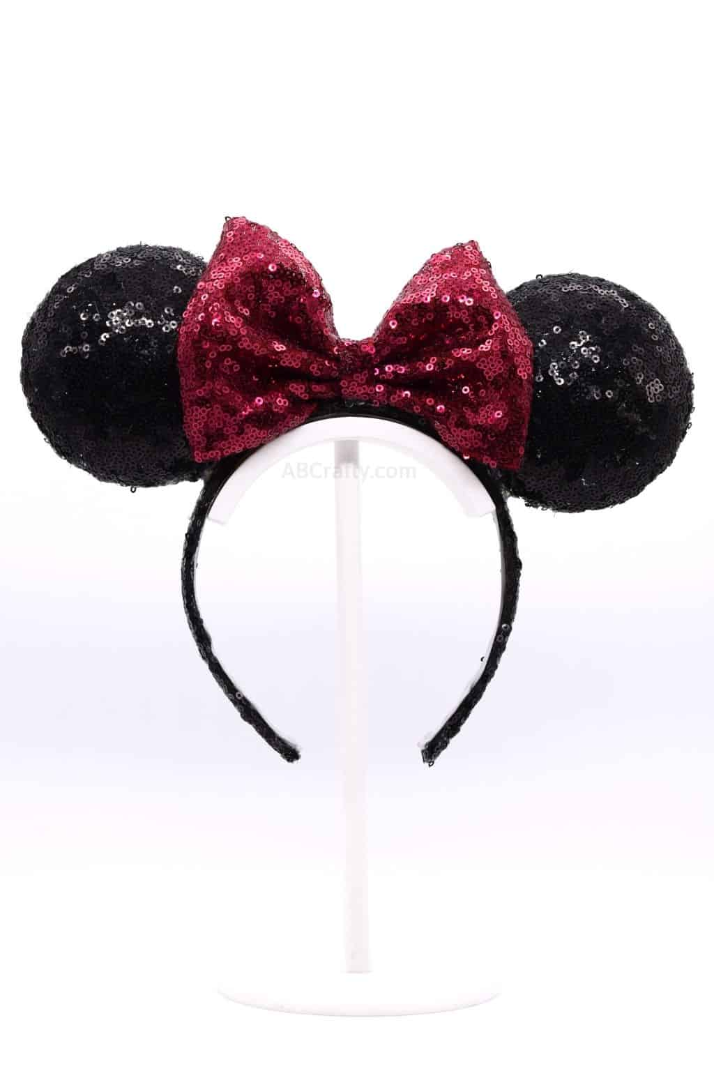 DIY Light Up Minnie Ears. It's a black sequined headband with a red sequined bow, creating the classic Disney Minnie Mouse ears
