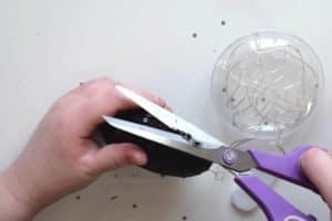 Trimming black sequin fabric glued to an plastic ornament using purple scissors