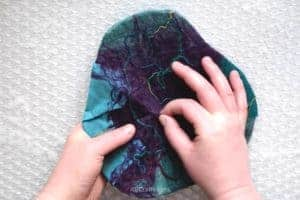 Doing the pinch test on lightly felted wool - using fingers to pinch the wool fiber and lifting it to see if it has felted