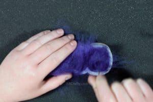 Using a felting needle to poke into purple wool inside of a cookie cutter in the shape of a marshmallow peep