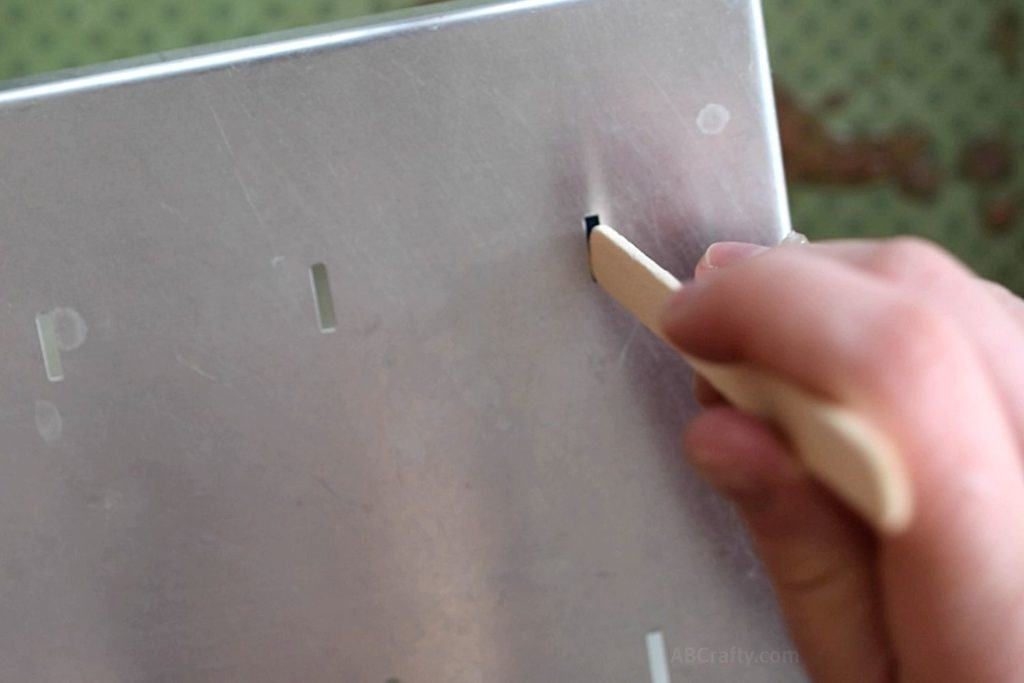Inserting a popsicle stick into the metal top of a popsicle mold