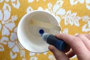 Squeezing blue soap dye into a paper cup that has melted clear glycerin soap