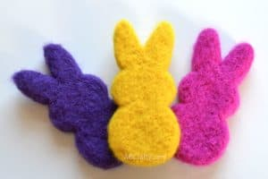 DIY catnip toys in the shape of marshmallow peeps in purple, yellow, and pink. All made of needle felted wool