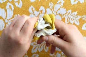 Mixing white and yellow mold putty together with hands