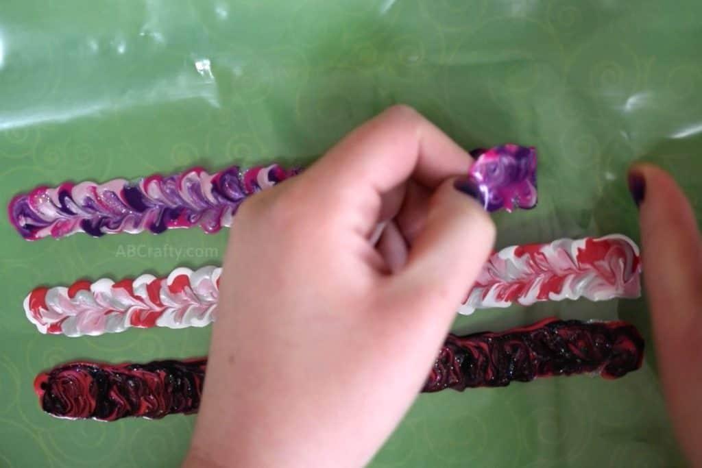 Peeling off stretchy fabric paint DIY bracelets from a plastic freezer bag