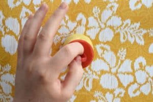 Placing a ring pop base into a yellow mold made of mold putty