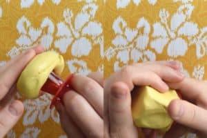 Squishing yellow putty around a red ring pop