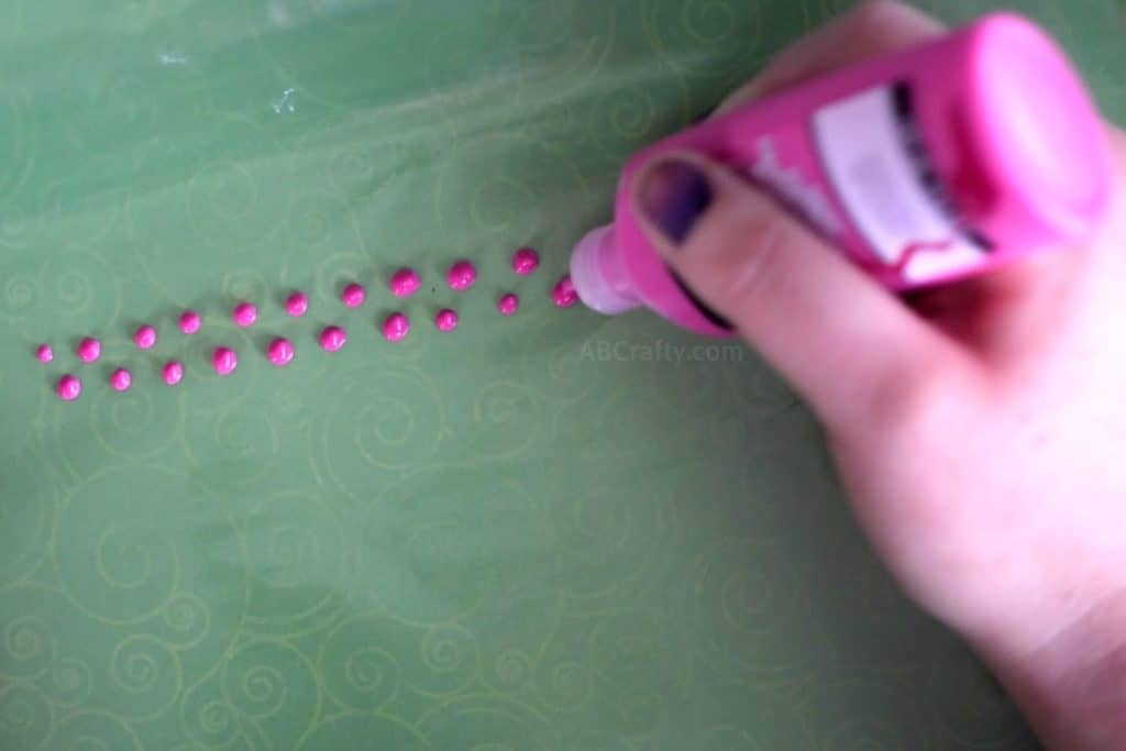 Painting two uneven rows of dots with pink fabric paint