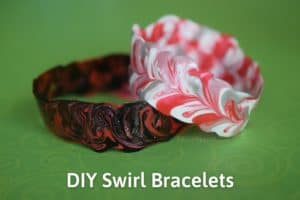 """Two bracelets made of fabric paint. One is red, silver, and white, and the other is black and red with glitter. The text reads """"DIY Swirl Bracelets"""""""