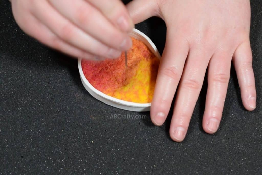Using a felting needle to felt colorful wool that is pink, orange, and yellow inside of an egg shaped cookie cutter