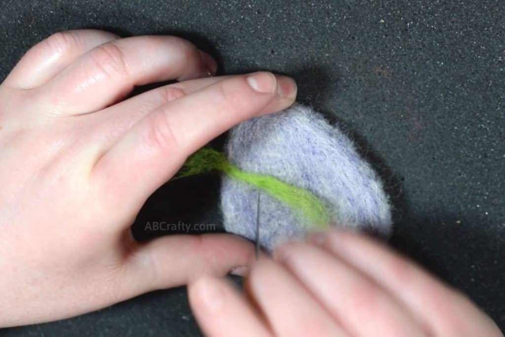Needle felting a stripe of green wool onto a purple felted egg cat toy