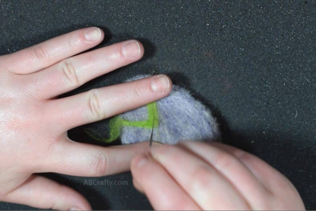 Needle felting a zig zag pattern with green wool onto a purple egg to make a felted Easter Egg