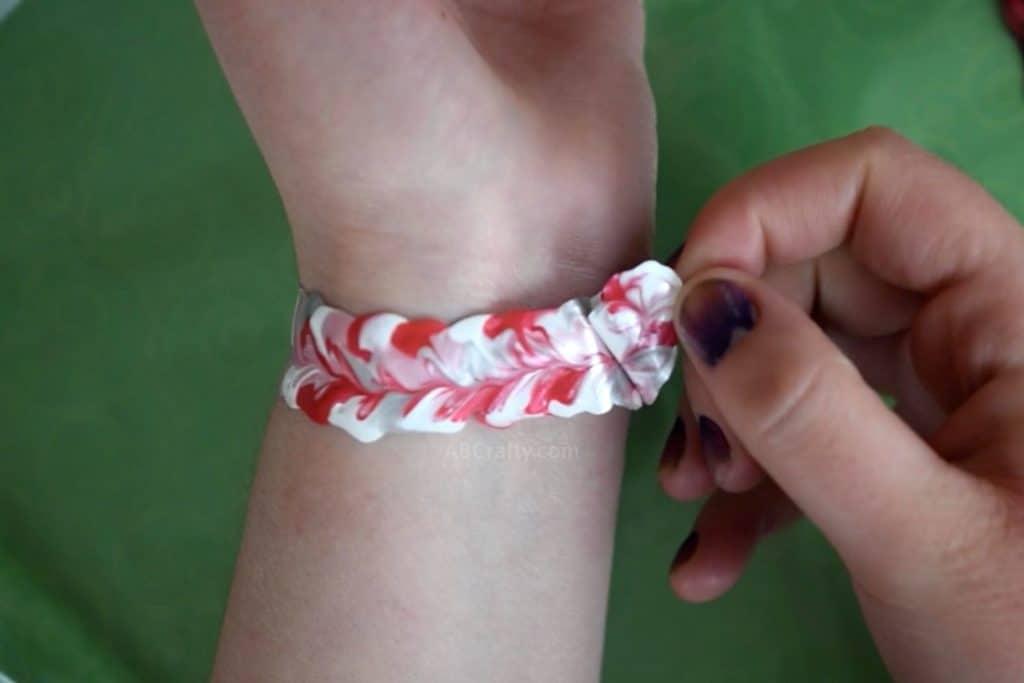 Peeling off white, pink, ready and glitter fabric paint swirl bracelet from around wrist
