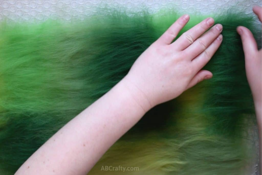 Placing green wool fiber in a rectangle over other green wool