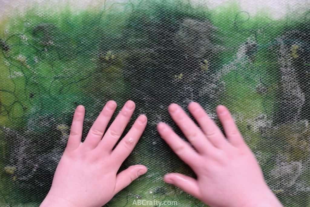 Rubbing hands over green wool and other fibers covered in mesh fabric