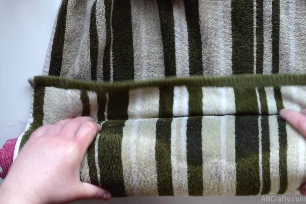 Tucking the end of a towel with green stripes under the edge of a pool noodle that it's wrapped around